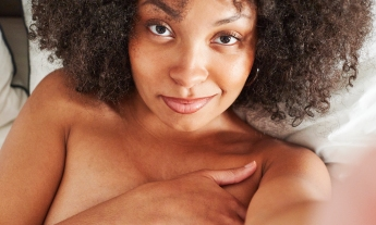 A Black woman takes a selfie where she smiles wryly at the camera. She is not wearing clothes and covers her chest with her hand. She has dark brown curly hair which frames her face, and is lying in a bed with white sheets.